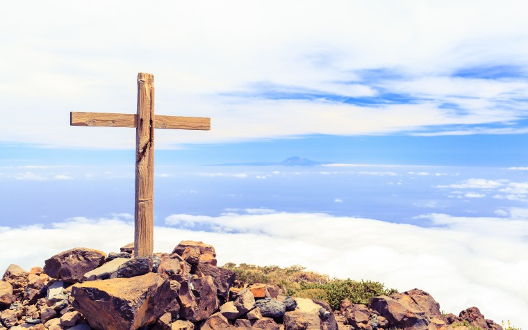 Christian wooden cross on mountain top rocky summit beautiful inspirational landscape with ocean island clouds and blue sky looking at scenic blue sea and white clouds.